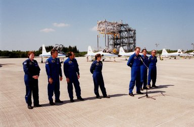 """After arriving at the Shuttle Landing Facility for launch preparations, the STS-101 crew pauses to greet the media. Standing (left to right) are Mission Specialists Susan Helms, James Voss, Yury Usachev of Russia and Mary Ellen Weber; Commander James Halsell; Pilot Scott """"Doc"""" Horowitz; and Mission Specialist Jeffrey Williams. The mission will take the crew to the International Space Station, delivering logistics and supplies, plus preparing the Station for the arrival of the Zvezda Service Module, expected to be launched by Russia in July 2000. Also, the crew will conduct one space walk to perform maintenance on the Space Station. This will be the third assembly flight for the Space Station. Launch is targeted for April 24 at about 4:15 p.m. EDT from Launch Pad 39A"""