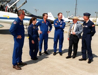 """The STS-101 crew is greeted by Center Director Roy Bridges and USAF Brig. Gen. Ron Sega, after the crew's arrival at the Shuttle Landing Facility to get ready for launch. Standing (left to right) on the tarmac are Mission Specialists Jeffrey Williams and Mary Ellen Weber, Pilot Scott """"Doc"""" Horowitz, Commander James Halsell, Bridges and Gen. Sega. Other crew members not shown are Mission Specialists James Voss, Susan Helms and Yury Usachev of Russia. The mission will take the crew to the International Space Station, delivering logistics and supplies, plus preparing the Station for the arrival of the Zvezda Service Module, expected to be launched by Russia in July 2000. Also, the crew will conduct one space walk to perform maintenance on the Space Station. This will be the third assembly flight for the Space Station. Launch is targeted for April 24 at about 4:15 p.m. EDT from Launch Pad 39A"""