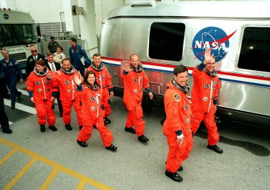Waving to onlookers, the STS-101 crew eagerly walk to the waiting Astrovan that will take them to Launch Pad 39A and liftoff of Space Shuttle Atlantis, targeted for 4:15 p.m. EDT. In their orange launch and entry suits, they are (in the f ront, left to right) Mission Specialists Susan Helms, Yuri Usachev of Russia and Mary Ellen Weber, plus Pilot Scott J. Horowitz; (in the rear, left to right) Mission Specialists James S. Voss and Jeffrey N. Williams, plus Commander James D. Halsell Jr. The mission will take the crew to the International Space Station to deliver logistics and supplies and to prepare the Station for the arrival of the Zvezda Service Module, expected to be launched by Russia in July 2000. Also, the crew will conduct one space walk. This will be the third assembly flight to the Space Station. The mission is expected to last about 10 days, with Atlantis landing at KSC Thursday, May 4, about 11:23 a.m. EDT