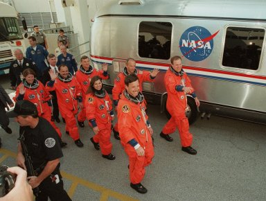 Smiling and waving to onlookers, the STS-101 crew eagerly walk to the waiting Astrovan that will take them to Launch Pad 39A a third time for launch of Space Shuttle Atlantis. From left are Mission Specialists Susan J. Helms, Yury Usachev of Russia, James S. Voss, Mary Ellen Weber and Jeffrey N. Williams; Pilot Scott J. Horowitz; and Commander James D. Halsell Jr. (pointing). The previous two launch attempts were scrubbed due to high cross winds at the Shuttle Landing Facility. The mission will take the crew to the International Space Station to deliver logistics and supplies and to prepare the Station for the arrival of the Zvezda Service Module, expected to be launched by Russia in July 2000. Also, the crew will conduct one space walk. This is the third assembly flight to the Space Station. After the 10-day mission, Atlantis is expected to land at KSC May 6 at about 12:03 p.m. EDT