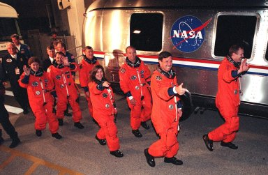 The STS-101 crew show their joy and eagerness to begin their mission as they had to the Astrovan for the trip to Launch Pad 39A and the fourth attempt at launch of Space Shuttle Atlantis. In their orange launch and entry suits, they are (left to right) Mission Specialists Susan J. Helms, Yury Usachev of Russia, James S. Voss, Mary Ellen Weber, Jeffrey N. Williams; Pilot Scott ?Doc? Horowitz; and Commander James D. Halsell Jr. The mission will take the crew to the International Space Station to deliver logistics and supplies and to prepare the Station for the arrival of the Zvezda Service Module, expected to be launched by Russia in July 2000. Also, the crew will conduct one space walk and will reboost the space station from 230 statute miles to 250 statute miles. This will be the third assembly flight to the Space Station. Liftoff of Space Shuttle Atlantis for the 10-day mission is scheduled for about 6:11 a.m. EDT from Launch Pad 39A. Landing is targeted for May 29 at 2:19 a.m. EDT