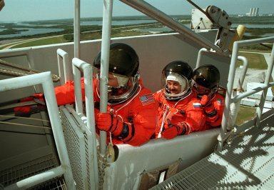 KENNEDY SPACE CENTER, FLA. -- Seated in a slidewire basket at the 195-foot level of the Fixed Service Structure, Launch Pad 39A, are (left to right) STS-101 Mission Specialists James Voss, Yury Usachev of Russia and Susan J. Helms. Voss is reaching to pull the release lever that will send the basket shooting down the 1,200-foot slidewire to a bunker west of the launch pad. The crew is practicing emergency egress from the orbiter as part of Terminal Countdown Demonstration (TCDT) activities that include a simulated launch countdown and familiarization with the payload. During their mission to the International Space Station, the STS-101 crew will be delivering logistics and supplies, plus preparing the Station for the arrival of the Zvezda Service Module, expected to be launched by Russia in July 2000. Also, the crew will conduct one space walk to perform maintenance on the Space Station. This will be the third assembly flight to the Space Station. STS-101 is scheduled to launch April 24 at 4:15 p.m. from Launch Pad 39A