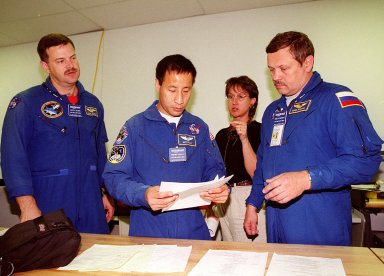 KENNEDY SPACE CENTER, FLA. -- Members of the STS-106 crew get information from a worker while looking over paperwork at SPACEHAB, Port Canaveral, Fla., about the payload on their mission to the International Space Station. From left (in uniform) are Pilot Scott Altman and Mission Specialists Edward Lu and Boris Morukov, who is with the Russian Space Agency. Among the payload is the Treadmill Vibration Isolation System (TVIS), a device to collect data on how vibrations imparted by crew exercise may be reduced or eliminated on the International Space Station. Those vibrations could disturb delicate microgravity experiments on the Space Station. During the mission, the crew will complete service module support tasks on orbit, transfer supplies and outfit the Space Station for the first long-duration crew. STS-106 is scheduled to launch Sept. 8