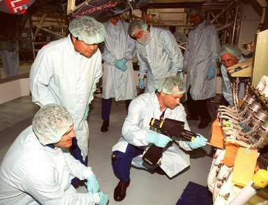 In the Space Station Processing Facility, members of the STS-92 crew check out equipment they will be using on the mission to the International Space Station. Here, (left to right) Mission Specialists Jeff Wisoff and Leroy Chiao watch while Michael Lopez-Alegria practices putting on and taking off fittings on the Z1 Integrated Truss Structure. In the background are Boeing technicians. The Z-1 truss, a component of the Station, is an early exterior framework to allow the first U.S. solar arrays on a future flight to be temporarily installed on Unity for early power. STS-92 is scheduled to launch Oct. 5 from launch Pad 39A