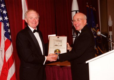 At a 50th anniversary gala capping a year-long celebration of 50 years of launches from Cape Canaveral Air Force Station, Center Director Roy Bridges (left) receives a plaque from committee chairman Ed Gormel. The plaque has a photo of the first rocket launch from Cape Canaveral Air Force Station (CCAFSj) and an anniversary patch below it that was flown on STS-99. The first launch at CCAFS took place at 9:28 a.m. on July 24, 1950, with the liftoff of Bumper 8 from Launch Complex 3. The gala, hosted by the Cape Canaveral Chapter Air Force Association, featured such speakers as Center Director Roy Bridges; Vice Commander, Air Force Space Command, Lt. Gen. Roger DeKok; and the Honorable David Weldon, U.S. representative of Florida?s 15th Congressional District