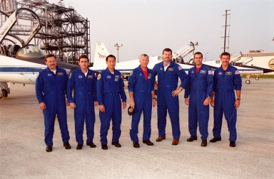 """KENNEDY SPACE CENTER, FLA. -- The STS-106 crew members pose on the tarmac at KSC's Shuttle Landing Facility after their arrival aboard the T-38 jets behind them. From left are Mission Specialists Boris V. Morukov, Yuri I. Malenchenko and Edward T. Lu; Commander Terrence W. Wilcutt; Pilot Scott D. Altman; and Mission Specialists Richard A. Mastracchio and Daniel C. Burbank. They will be taking part in Terminal Countdown Demonstration Test activities, which include emergency egress training and a simulated launch countdown. STS-106 is scheduled to launch Sept. 8, 2000, at 8:31 a.m. EDT from Launch Pad 39B. On the 11-day mission, the seven-member crew will perform support tasks on orbit, transfer supplies and prepare the living quarters in the newly arrived Zvezda Service Module. The first long-duration crew, dubbed """"Expedition One,"""" is due to arrive at the Station in late fall."""