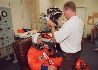 STS-106 Mission Specialist Daniel C. Burbank gets ready to put on his helmet, as part of fit check during Terminal Countdown Demonstration Test activities (TCDT). The TCDT also provides emergency egress training, simulated countdown exercises and opportunities for the crew to inspect the mission payloads in the orbiter?s payload bay. STS-106 is scheduled to launch Sept. 8, 2000, at 8:31 a.m. EDT from Launch Pad 39B. On the 11-day mission, the seven-member crew will perform support tasks on orbit, transfer supplies and prepare the living quarters in the newly arrived Zvezda Service Module. The first long-duration crew, dubbed ?Expedition One,? is due to arrive at the Station in late fall