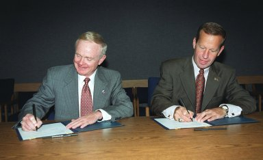 At the KSC Visitor Complex, Center Director Roy D. Bridges (left) and Florida?s Lieutenant Governor Frank T. Brogan sign a Memorandum of Understanding (MOU). The MOU documents the intent of NASA KSC and the State of Florida to form partnerships with academic institutions in Florida for development of aerospace-related advanced training and academic/educational programs. The three-year project anticipates that the partnership and educational programs fostered will improve the lifelong learning environment for the aerospace and engineering workforce