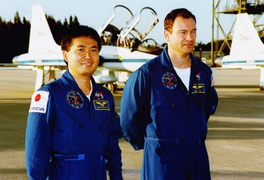 STS-92 Mission Specialists Koichi Wakata and Michael Lopez-Alegria pause on the tarmac after their arrival aboard the T-38 jet aircraft in the background. They and the rest of the crew are at KSC to take part in Terminal Countdown Demonstration Test (TCDT) activities. The TCDT includes emergency egress training from the orbiter and pad, plus a simulated countdown. The fifth mission to the International Space Station, STS-92 will carry the Integrated Truss Structure Z1, the first of the planned 10 trusses on the Space Station, and the third Pressurized Mating Adapter. The Z1 will allow the first U.S. solar arrays on a future flight to be temporarily installed on Unity for early power. PMA-3 will provide a Shuttle docking port for the solar array installation on the sixth ISS flight and Lab installation on the seventh ISS flight. STS-92 is scheduled to launch Oct. 5 from launch Pad 39A. It will be the 100th flight in the Shuttle program