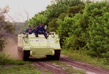 With other crew members in the back, STS-92 Mission Specialist Leroy Chiao races the M-113 along the track through the scrub. Driving the M-113 is part of emergency egress training during Terminal Countdown Demonstration Test (TCDT) activities. The tracked vehicle could be used by the crew in the event of an emergency at the pad during which the crew must make a quick exit from the area. The TCDT also provides simulated countdown exercises and opportunities to inspect the mission payloads in the orbiter?s payload bay. STS-92 is scheduled to launch Oct. 5 at 9:30 p.m. EDT on the fifth flight to the International Space Station. It will carry two elements of the Space Station, the Integrated Truss Structure Z1 and the third Pressurized Mating Adapter. The mission is also the 100th flight in the Shuttle program