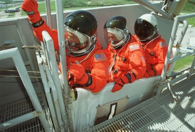 KENNEDY SPACE CENTER, FLA. -- Seated in the slidewire basket at the 195-foot level of the Fixed Service Structure on Launch Pad 39A, STS-92 Mission Specialists Leroy Chiao, Peter J.K. ?Jeff? Wisoff and Michael E. Lopez-Alegria practice emergency egress. They and other crew members have been taking part in Terminal Countdown Demonstration Test activities that also include a simulated countdown. STS-92 is scheduled to launch Oct. 5 at 9:38 p.m. EDT on the fifth flight to the International Space Station. It will carry two elements of the Space Station, the Integrated Truss Structure Z1 and the third Pressurized Mating Adapter. The mission is also the 100th flight in the Shuttle program