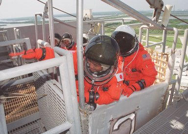 KENNEDY SPACE CENTER, FLA. -- STS-92 Mission Specialist Koichi Wakata of Japan reaches for a lever that will release the slidewire basket he is in. Behind him is Mission Specialist William S. McArthur Jr. In another basket (in the background) are Mission Specialists Leroy Chiao, Peter J.K. ?Jeff? Wisoff and Michael E. Lopez-Alegria. They are taking part in emergency egress training, one of the Terminal Countdown Demonstration Test activities that also include a simulated countdown. STS-92 is scheduled to launch Oct. 5 at 9:38 p.m. EDT on the fifth flight to the International Space Station. It will carry two elements of the Space Station, the Integrated Truss Structure Z1 and the third Pressurized Mating Adapter. The mission is also the 100th flight in the Shuttle program