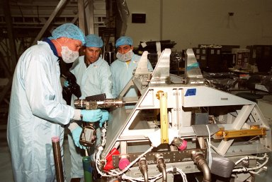 In the Space Station Processing Facility, STS-100 Commander Kent Rominger (left) tries out a piece of equipment while a worker (center) gives directions. Looking on at right is Mission Specialist Umberto Guidoni, with the European Space Agency. Mission STS-100, scheduled to launch April 19, 2001, will include Raffaello as well as the Space Station Remote Manipulator System (SSRMS) as its payload. MPLMs are pressurized modules that will serve as the International Space Station's ?moving vans,? carrying laboratory racks filled with equipment, experiments and supplies to and from the station aboard the Space Shuttle. The SSRMS is the primary means of transferring payloads between the orbiter payload bay and the International Space Station for assembly