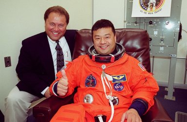 During suitup in the Operations and Checkout Building, STS-92 Mission Specialist Leroy Chiao gives thumbs up for launch. With him (left) is VITT Mission Lead Roland Nedelkovich, from Houston. During the 11-day mission to the International Space Station, four extravehicular activities (EVAs), or spacewalks, are planned for construction. The payload includes the Integrated Truss Structure Z-1 and the third Pressurized Mating Adapter. The Z-1 truss is the first of 10 that will become the backbone of the Space Station, eventually stretching the length of a football field. PMA-3 will provide a Shuttle docking port for solar array installation on the sixth Station flight and Lab installation on the seventh Station flight. Launch is scheduled for 7:17 p.m. EDT. Landing is expected Oct. 22 at 2:10 p.m. EDT