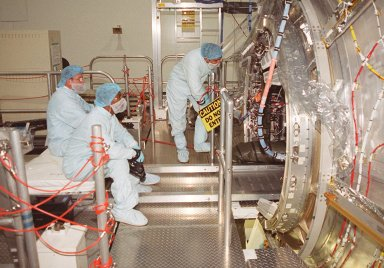 In the Space Station Processing Facility, workers at left watch while members of the STS-98 crew check out equipment inside the U.S. Lab, Destiny (at right). The crew comprises Commander Ken Cockrell, Pilot Mark Polansky and Mission Specialists Robert Curbeam, Thomas Jones and Marsha Ivins. They are taking part in Crew Equipment Interface Test activities, becoming familiar with equipment they will be handling during the mission. The mission will be transporting the Lab to the International Space Station with five system racks already installed inside of the module. With delivery of electronics in the lab, electrically powered attitude control for Control Moment Gyroscopes will be activated. The STS-98 launch is scheduled for Jan. 18, 2001
