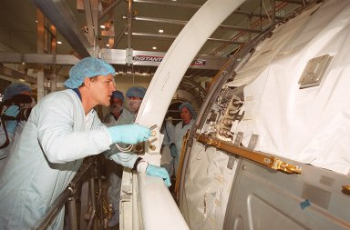 In the Space Station Processing Facility, STS-100 Mission Specialist Scott Parazynski looks over part of the U.S. Lab, Destiny. Mission STS-100 will be the ninth construction flight for the International Space Station. It is scheduled to launch April 19, 2001