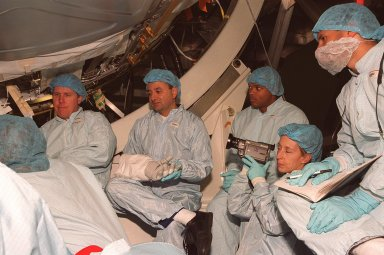 In the Space Station Processing Facility, members of the STS-98 crew, sitting in front of the U.S. Lab, Destiny, listen to a trainer during Crew Equipment Interface Test (CEIT) activities. Seen, left to right, are Mission Specialist Thomas Jones, Pilot Mark Polansky and Mission Specialists Robert Curbeam and Marsha Ivins (with camera). The CEIT allows a crew to become familiar with equipment they will be handling during the mission. With launch scheduled for Jan. 18, 2001, the STS-98 mission will be transporting the Lab to the International Space Station with five system racks already installed inside of the module. After delivery of electronics in the lab, electrically powered attitude control for Control Moment Gyroscopes will be activated