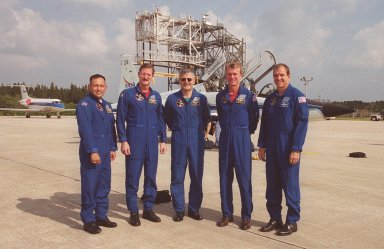 After their arrival at the Shuttle Landing Facility, the STS-97 crew pose for a photo on the parking area. Behind them are the T-38 jet aircraft that brought them. From left, they are Mission Specialist Carlos Noriega, Joe Tanner and Marc Garneau (with the Canadian Space Agency); Commander Brent Jett; and Pilot Mike Bloomfield. The crew is at KSC to take part in Terminal Countdown Demonstration Test activities that include emergency egress training, familiarization with the payload, and a simulated launch countdown. In the background, top, is the mate/demate device that is used to load or unload an orbiter from the back of the Shuttle Carrier Aircraft. In the background left is a Shuttle Training Aircraft. Mission STS-97is the sixth construction flight to the International Space Station. Its payload includes the P6 Integrated Truss Structure and a photovoltaic (PV) module, with giant solar arrays that will provide power to the Station. The mission includes two spacewalks to complete the solar array connections. STS-97 is scheduled to launch Nov. 30 at about 10:05 p.m. EST