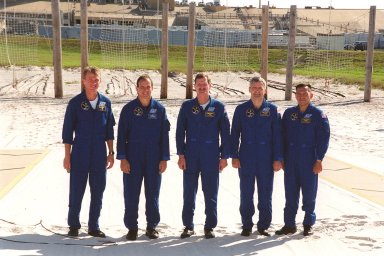 Standing in the slidewire landing zone at Launch Pad 39B, the STS-97 crew respond to questions from the media. They are, left to right, Commander Brent Jett, Pilot Mike Bloomfield and Mission Specialists Joe Tanner, Marc Garneau and Carlos Noriega. Garneau is with the Canadian Space Agency. The nets suspended behind them are a braking system catch net for the slidewire baskets that provide emergency exit from the orbiter and Fixed Service Structure. The crew is at KSC to take part in Terminal Countdown Demonstration Test activities that include emergency egress training, familiarization with the payload, and a simulated launch countdown. Mission STS-97is the sixth construction flight to the International Space Station. Its payload includes the P6 Integrated Truss Structure and a photovoltaic (PV) module, with giant solar arrays that will provide power to the Station. The mission includes two spacewalks to complete the solar array connections. STS-97 is scheduled to launch Nov. 30 at 10:05 p.m. EST