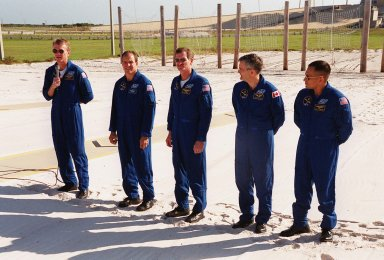 KENNEDY SPACE CENTER, Fla. -- Standing in the slidewire landing zone at Launch Pad 39B, the STS-97 crew respond to questions from the media. Commander Brent Jett (on left, with microphone) introduces the rest of the crew (left to right) Pilot Mike Bloomfield and Mission Specialists Joe Tanner, Marc Garneau and Carlos Noriega. Garneau is with the Canadian Space Agency. The nets suspended behind them are a braking system catch net for the slidewire baskets that provide emergency exit from the orbiter and Fixed Service Structure. The crew is at KSC to take part in Terminal Countdown Demonstration Test activities that include emergency egress training, familiarization with the payload, and a simulated launch countdown. Mission STS-97is the sixth construction flight to the International Space Station. Its payload includes the P6 Integrated Truss Structure and a photovoltaic (PV) module, with giant solar arrays that will provide power to the Station. The mission includes two spacewalks to complete the solar array connections. STS-97 is scheduled to launch Nov. 30 at about 10:05 p.m. EST