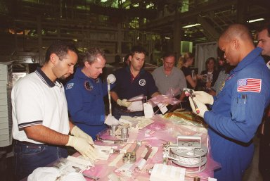 KENNEDY SPACE CENTER, FLA. -- In Orbiter Processing Facility bay 3, STS-98 Mission Specialists Tom Jones (second from left) and Robert Curbeam (right) test tools that will be used during extravehicular activities (EVA) on their mission. Scheduled for launch Jan. 18, 2001, STS-98 will be transporting the U.S. Lab, Destiny, to the International Space Station with five system racks already installed inside of the module. After delivery of electronics in the lab, electrically powered attitude control for Control Moment Gyroscopes will be activated