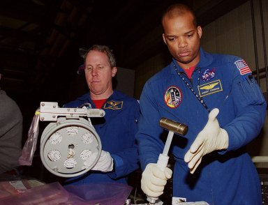KENNEDY SPACE CENTER, FLA. -- In Orbiter Processing Facility bay 3, STS-98 Mission Specialists Tom Jones and Robert Curbeam test tools that will be used during extravehicular activities (EVA) on their mission. Scheduled for launch Jan. 18, 2001, STS-98 will be transporting the U.S. Lab, Destiny, to the International Space Station with five system racks already installed inside of the module. After delivery of electronics in the lab, electrically powered attitude control for Control Moment Gyroscopes will be activated