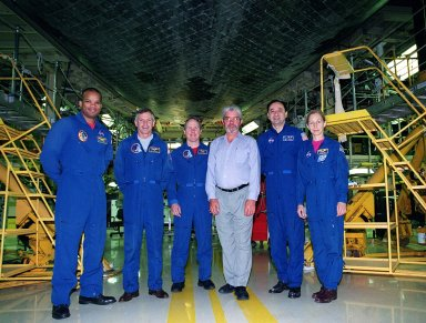 KENNEDY SPACE CENTER, FLA. -- The STS-98 crew, with United Space Alliance worker Larry Oshein (center), poses underneath orbiter Atlantis in Orbiter Processing Facility bay 3. From left, they are Mission Specialist Robert Curbeam, Commander Ken Cockrell, Mission Specialist Tom Jones, Oshein, and Mission Specialists Mark Polansky and Marsha Ivins. The crew is at KSC for Crew Equipment Interface Test activities. Launch of Atlantis on mission STS-98 is scheduled for Jan. 18, 2001. It will be transporting the U.S. Lab, Destiny, to the International Space Station with five system racks already installed inside of the module. After delivery of electronics in the lab, electrically powered attitude control for Control Moment Gyroscopes will be activated
