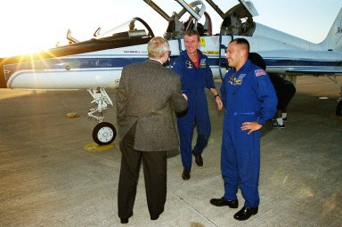 At the Shuttle Landing Facility, Center Director Roy Bridges (left) greets STS-97 Commander Brent Jett on his arrival at KSC for the mission launch. At right is Mission Specialist Carlos Noriega. Jett and Noriega traveled from Johnson Space Center, Houston, Texas, in the T-38 jet aircraft behind them. Mission STS-97is the sixth construction flight to the International Space Station. Its payload includes the P6 Integrated Truss Structure and a photovoltaic (PV) module, with giant solar arrays that will provide power to the Station. The mission includes two spacewalks to complete the solar array connections. STS-97 is scheduled to launch Nov. 30 at about 10:06 p.m. EST