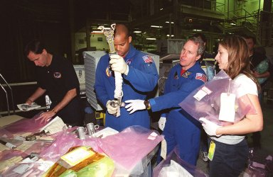 KENNEDY SPACE CENTER, FLA. -- In the Orbiter Processing Facility, STS-98 Mission Specialists Robert Curbeam (center left) and Tom Jones (center right) practice with tools that will be used on extravehicular activities on their mission. The STS-98 crew is at KSC for Crew Equipment Interface Test activities. Launch on mission STS-98 is scheduled for Jan. 18, 2001. It will be transporting the U.S. Lab, Destiny, to the International Space Station with five system racks already installed inside of the module. After delivery of electronics in the lab, electrically powered attitude control for Control Moment Gyroscopes will be activated