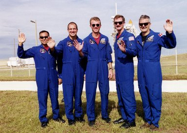 The STS-97 crew members wave for the camera as they gather outside Launch Pad 39B. Standing left to right are Mission Specialist Carlos Noriega, Pilot Michael Bloomfield, Commander Brent Jett and Mission Specialists Joseph Tanner and Marc Garneau, who is with the Canadian Space Agency. Behind Tanner can be seen the top of the external tank. The mission to the International Space Station carries the P6 Integrated Truss Segment containing solar arrays and batteries that will be temporarily installed to the Unity connecting module by the Z1 truss, recently delivered to and installed on the Station on mission STS-92. The two solar arrays are each more than 100 feet long. They will capture energy from the sun and convert it to power for the Station. Two spacewalks will be required to install the solar array connections. STS-97 is scheduled to launch Nov. 30 at about 10:06 p.m. EST