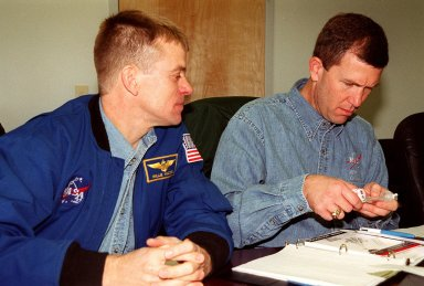KENNEDY SPACE CENTER, FLA. -- STS-107 Pilot William C. ?Willie? McCool (left) and Commander Rick D. Husband look over equipment for their mission. They and other crew members are taking part in In-Flight Maintenance training. Research mission STS-107, scheduled to launch July 19, 2001, will carry the SPACEHAB Double Module in its first research flight into space and a broad collection of experiments ranging from material science to life science