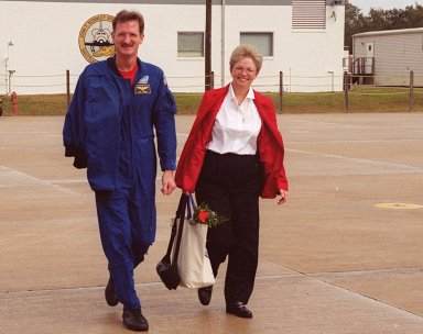 KENNEDY SPACE CENTER, FLA. -- After a night?s rest and a brief press conference at KSC, STS-97 Mission Specialist Joseph Tanner heads for the plane at the Shuttle Landing Facility. With him is his wife. They and other crew members and their families are returning to Houston. Mission STS-97 ended on Dec. 11, 2000, with a landing at KSC at 6:04 p.m. EST