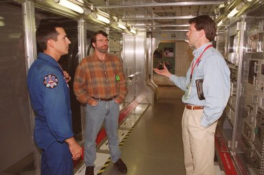 """KENNEDY SPACE CENTER, FLA. -- Astronaut John Herrington (left) and Norm Abram, of television?s """"This Old House"""" and """"The New Yankee Workshop,"""" talk to Phil West, of Johnson Space Center. They are standing in front of a mockup of the U.S. Lab, located in the International Space Station Center, a tour facility.. Abram is at KSC to film an episode of """"This Old House."""