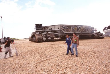 Astronaut John Herrington (center) and master carpenter on This Old House, Norm Abram, are filmed walking in front of a crawler-transporter near the Launch Control Center (far right). The cast and crew of This Old House are filming at KSC for an episode of the show. Herrington is accompanying the film crew on their tour of KSC