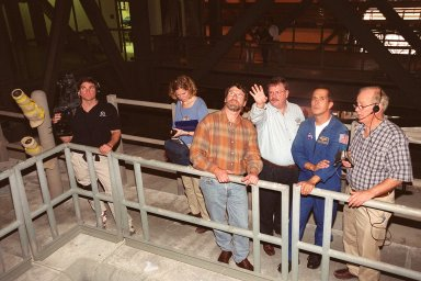 Members of the crew of the television series This Old House get a close look at Space Shuttle Atlantis in the Vehicle Assembly Building. In the center is Norm Abram, master carpenter on the series. Second from the right is astronaut John Herrington, who is accompanying the film crew on their tour of KSC. The cast and crew of This Old House are filming at KSC for an episode of the show