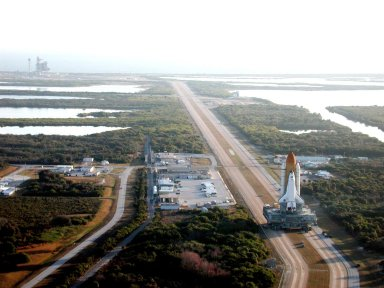 KENNEDY SPACE CENTER, Fla. -- As the early morning light casts a glow over the landscape, Space Shuttle Atlantis moves slowly along the crawlerway for the trek to Launch Pad 39A (upper left). The Shuttle has been in the VAB undergoing tests on the solid rocket booster cables. A prior extensive evaluation of NASA?s SRB cable inventory on the shelf revealed conductor damage in four (of about 200) cables. Shuttle managers decided to prove the integrity of the system tunnel cables already on Atlantis, causing return of the Shuttle to the VAB a week ago. Launch of Atlantis on STS-98 has been rescheduled to Feb. 7 at 6:11 p.m. EST
