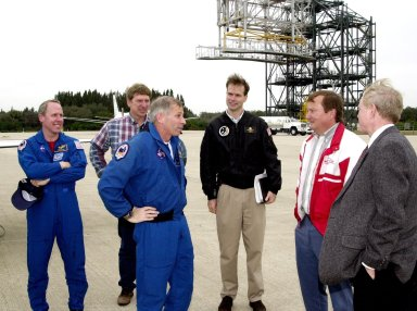 KENNEDY SPACE CENTER, FLA. -- STS-98 Mission Commander Kenneth Cockrell (center) talks with Launch Director Michael Leinbach (red and white jacket) and Center Director Roy Bridges (right) at the Shuttle Landing Facility after the crew's arrival Sunday to complete preparations for launch.; Behind him are, from left to right, Mission Specialist Thomas Jones; Tom Kwiatkowski, NASA, Johnson Space Center (JSC); and Robert Hanley, United Space Alliance, JSC.; The crew also includes Pilot Mark Polansky and Mission Specialists Marsha Ivins and Robert Curbeam.; STS-98 is the seventh construction flight to the International Space Station, carrying as payload the U.S. Lab Destiny, a key element in the construction of the ISS. Launch of STS-98 is scheduled for Feb. 7 at 6:11 p.m. EST