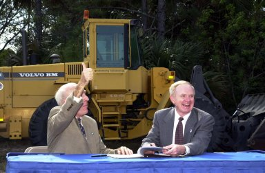 During a signing ceremony, Ed Gormel (left), executive director of Spaceport Florida Authority, and Roy Bridges Jr., Center Director, respond to a remark from the audience. The two are signing a SERPL Real Property Use Permit Agreement between the two organizations to construct a three-mile roadway. It is the start of a construction project that includes the Space Experiment Research & Processing Laboratory (SERPL). The signing took place outdoors on S.R. 3 prior to a groundbreaking ceremony for the roadway. The road, to be known as Space Commerce Way, will serve the public by providing a 24-hour access route through KSC from S.R. 3 to the NASA Causeway and KSC Visitor Complex. The SERPL project is enabled by a partnership and collaboration between NASA and the State of Florida to create a vital resource for international and commercial space customers. SERPL is considered a magnet facility, and will support the development and processing of life sciences experiments destined for the International Space Station and accommodate NASA, industry and academic researchers performing associated biological research