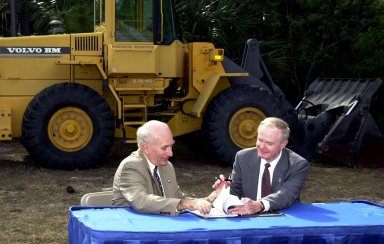 Ed Gormel (left), executive director of Spaceport Florida Authority, and Roy Bridges Jr., Center Director, get ready to sign a SERPL Real Property Use Permit Agreement between the two organizations to construct a three-mile roadway. It is the start of a construction project that includes the Space Experiment Research & Processing Laboratory (SERPL). The signing took place outdoors on S.R. 3 prior to a groundbreaking ceremony for the roadway. The road, to be known as Space Commerce Way, will serve the public by providing a 24-hour access route through KSC from S.R. 3 to the NASA Causeway and KSC Visitor Complex. The SERPL project is enabled by a partnership and collaboration between NASA and the State of Florida to create a vital resource for international and commercial space customers. SERPL is considered a magnet facility, and will support the development and processing of life sciences experiments destined for the International Space Station and accommodate NASA, industry and academic researchers performing associated biological research