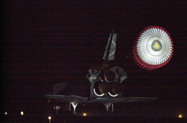 KENNEDY SPACE CENTER, Fla. -- With the drag chute reflected in the bright lights at the Shuttle Landing Facility, Atlantis prepares to land on Runway 15 at the Shuttle Landing Facility to complete a 12-day, 18-hour, 34-minute-long STS-104 mission. Main gear touchdown occurred at 11:38:55 p.m. EDT. At the controls is Commander Steven W. Lindsey. Other crew members on board are Pilot Charles Hobaugh and Mission Specialists Michael Gernhardt, Janet Lynn Kavandi and James F. Reilly. This is the 18th nighttime landing for a Space Shuttle, the 13th at Kennedy Space Center. The mission delivered the Joint Airlock Module to the International Space Station, completing the second phase of the assembly of the Space Station