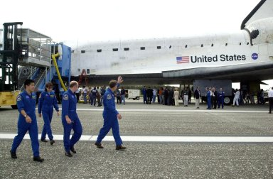 KENNEDY SPACE CENTER, FLA. -- The STS-108 crew wave to the crowd as they head for the van to transport them back to crew quarters. The crew completed their mission with a successful landing on Runway 15 of the KSC Shuttle Landing Facility. The mission had an elapsed time of 11 days, 19 hours and 35 minutes. Main gear touchdown occurred at 12:55:10 p.m. EST (17:55:10 GMT), nose gear touchdown at 12:55:23 p.m. (17:55:23 GMT) , wheel stop at 12:56:13 p.m. (17:56:13 GMT). Rollout distance was 8,941 feet. Endeavour carried both the mission crew and the Expedition 3 crew - Commander Frank Culbertson and cosmonauts Vladimir Dezhurov and Mikhail Tyurin - who returned to Earth after 129 days in space on the Space Station. STS-108 was the 12th mission to the International Space Station. This mission was the 107th flight in the Shuttle program and the 17th flight for the orbiter. The landing is the 57th at KSC in the history of the program
