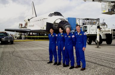 KENNEDY SPACE CENTER, FLA. -- After a successful return to Earth aboard orbiter Endeavour (background), the STS-108 crew pose for a photo. From left are Mission Specialists Daniel M. Tani and Linda A. Godwin, Pilot Mark E. Kelly and Commander Dominic L. Gorie. The mission had an elapsed time of 11 days, 19 hours and 35 minutes. Main gear touchdown occurred at 12:55:10 p.m. EST (17:55:10 GMT), nose gear touchdown at 12:55:23 p.m. (17:55:23 GMT) , wheel stop at 12:56:13 p.m. (17:56:13 GMT). STS-108 was the 12th mission to the International Space Station. This mission was the 107th flight in the Shuttle program and the 17th flight for the orbiter. The landing is the 57th at KSC in the history of the program. Endeavour carried both the mission crew and the Expedition 3 crew - Commander Frank Culbertson and cosmonauts Vladimir Dezhurov and Mikhail Tyurin - who returned to Earth after 129 days in space on the Space Station