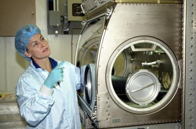 """KENNEDY SPACE CENTER, FLA. -- Astronaut Peggy Whitson, a member of the Expedition 5 crew, points to a part of the equipment she is using as part of familiarization for the mission. She and other crew members Commander Valeri Korzun and Sergei Treschev will be traveling to the International Space Station on mission STS-111 and will be replacing the Expedition 4 crew. Part of the payload on STS-111 will be the Mobile Base System, to be installed installed on the Mobile Transporter to complete the Canadian Mobile Servicing System, or MSS. The mechanical arm will then have the capability to """"inchworm"""" from the U.S. Lab fixture to the MSS and travel along the Truss to work sites. STS-111 is scheduled to launch in May 2002"""