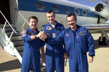 KENNEDY SPACE CENTER, FLA. -- The Expedition Three crew clasp hands in a show of unity before they depart KSC for Houston. From left to right are Commander Frank Culbertson and cosmonauts Vladimir Dezhurov and Mikhail Tyurin. The three returned to Earth as passengers aboard the orbiter Endeavour, which landed at KSC at 12:55 p.m. EST (17:55 GMT) Dec. 17, 2001, after completing mission STS-108. Expedition 3 had spent 129 days on the International Space Station. The landing is the 57th at KSC in the history of the program STS-108 was the 12th mission to the Space Station. This mission was the 107th flight in the Shuttle program and the 17th flight for the orbiter
