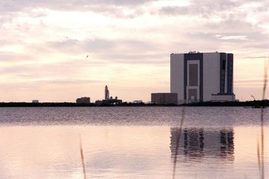 KENNEDY SPACE CENTER, Fla. -- Under cloudy skies, Space Shuttle Atlantis inches its way to Launch Pad 39A from the Vehicle Assembly Building (right). The journey is a distance of just over 3 miles. The water in the foreground is part of Banana Creek. Atlantis will fly on mission STS-98, the seventh construction flight to the International Space Station. The orbiter will carry in its payload bay the U.S. Laboratory, named Destiny, that will have five system racks already installed inside the module. After delivery of electronics in the lab, electrically powered attitude control for Control Moment Gyroscopes will be activated. Atlantis is scheduled for launch no earlier than Jan. 19, 2001, with a crew of five