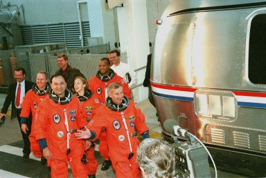 The STS-98 crew wave to onlookers as they walk out of the Operations and Checkout Building dressed for a simulated launch countdown at Launch Pad 39A. From left to right, they are Mission Specialist Thomas Jones, Pilot Mark Polansky, Mission Specialists Marsh Ivins and Robert Curbeam, being led by Commander Ken Cockrell. The crew is taking part in Terminal Countdown Demonstration Test activities, which include the countdown and emergency egress training at the pad. STS-98 is the seventh construction flight to the International Space Station, carrying as payload the U.S. Lab Destiny, a key element in the construction of the ISS. Launch of STS-98 is scheduled for Jan. 19 at 2:11 a.m. EST