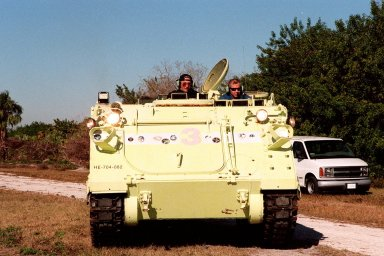 Capt. George Hoggard (left), a training officer with SGS Fire Services, sits alongside STS-98 Commander Ken Cockrell, who practices driving an M-113 armored carrier. In the event of an emergency at the pad prior to launch, the carrier could be used to transport the crew to a nearby bunker or farther. The vehicle is part of emergency egress training at Launch Pad 39A. The STS-98 crew is at KSC to take part in Terminal Countdown Demonstration Test activities, which also includes a simulated launch countdown. STS-98 is the seventh construction flight to the International Space Station, carrying as payload the U.S. Lab Destiny, a key element in the construction of the ISS