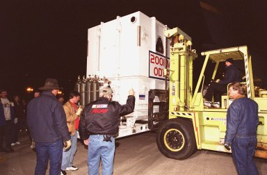 A forklift carries the crated Mars Odyssey spacecraft from the Air Force C-17 cargo airplane that brought it from Denver, Colo.., location of the Lockheed Martin plant where the spacecraft was built. The crate will placed on a transport trailer to take it from KSC?s Shuttle Landing Facility to the Spacecraft Assembly and Encapsulation Facility 2 (SAEF-2) located in the KSC Industrial Area. In the SAEF it will undergo final assembly and checkout. This includes installation of two of the three science instruments, integration of the three-panel solar array, and a spacecraft functional test. It will be fueled and then mated to an upper stage booster, the final activities before going to the launch pad. Launch is planned for April 7, 2001 the first day of a 21-day planetary window. Mars Odyssey will be inserted into an interplanetary trajectory by a Boeing Delta II launch vehicle from Pad A at Complex 17 at the Cape Canaveral Air Force Station, Fla. The spacecraft will arrive at Mars on Oct. 20, 2001, for insertion into an initial elliptical capture orbit. Its final operational altitude will be a 250-mile-high, Sun-synchronous polar orbit. Mars Odyssey will spend two years mapping the planet's surface and measuring its environment