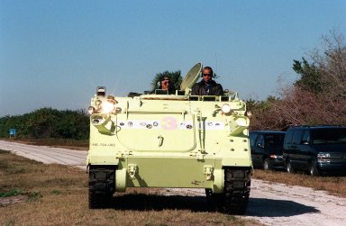 STS-98 Mission Specialist Robert Curbeam (right) takes a turn driving an M-113 armored carrier, part of emergency egress training at Launch Pad 39A. Seated alongside is Capt. George Hoggard (left), a training officer with SGS Fire Services. In the event of an emergency at the pad prior to launch, the carrier could be used to transport the crew to a nearby bunker or farther. The STS-98 crew is at KSC to take part in Terminal Countdown Demonstration Test activities, which also includes a simulated launch countdown. STS-98 is the seventh construction flight to the International Space Station, carrying as payload the U.S. Lab Destiny, a key element in the construction of the ISS