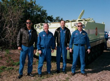 Members of the STS-98 crew pose in front of the M-113 armored carrier they were test driving as part of emergency egress training at Launch Pad 39A. From left are Mission Specialists Robert Curbeam and Thomas Jones, Pilot Mark Polansky and Commander Ken Cockrell. Not pictured is the fifth crew member, Mission Specialist Marsha Ivins. The carrier could be used to transport the crew to a nearby bunker, or farther, in the event of an emergency at the pad prior to launch. The STS-98 crew is at KSC to take part in Terminal Countdown Demonstration Test activities, which also includes a simulated launch countdown. STS-98 is the seventh construction flight to the International Space Station, carrying as payload the U.S. Lab Destiny, a key element in the construction of the ISS